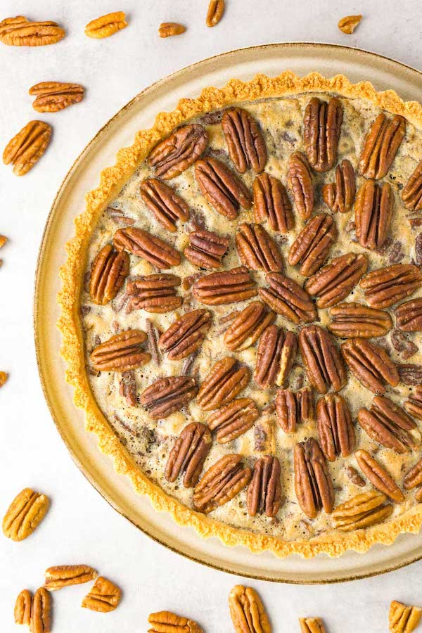 View from above on a freshly baked low carb pecan pie, pecan halves are lying around.