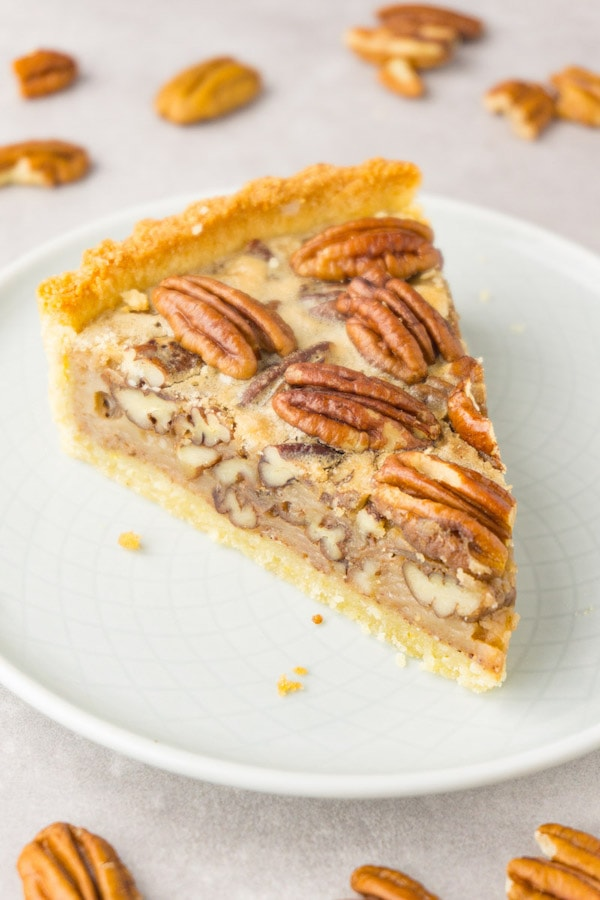 A slice of pecan pie served on a small round plate, pecan halves are lying around.