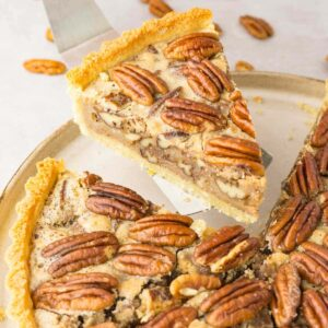 Close up shot of partially sliced sugar-free pecan pie, one piece is on a silver pie server.