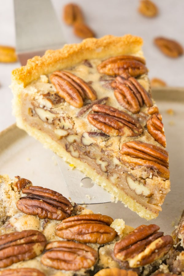 Close up shot of a piece of pecan pie being taken from the rest of the pie with a silver pie server.