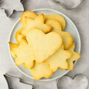 View from above on a small round plate filled with cut out Christmas cookies, cookie cutters are lying around.