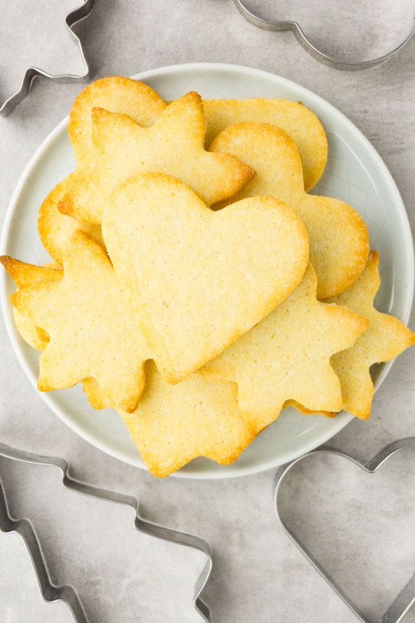 A small round plate filled with sugar cookies of different shapes, cookie cutters are lying around.