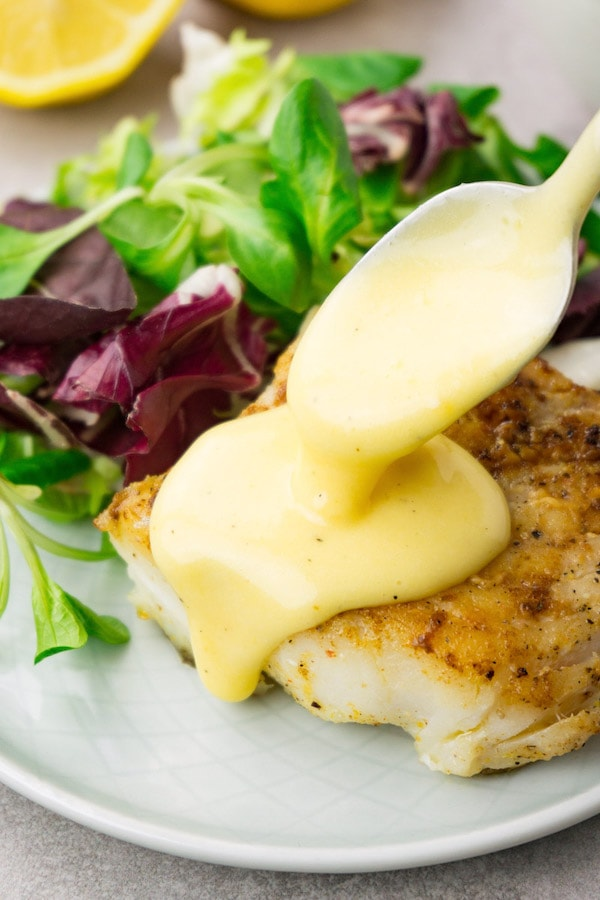 Pouring hollandaise sauce from a spoon on top of a piece of fried cod with fresh green salad as a side dish.
