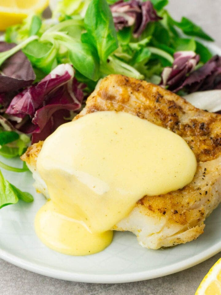 Close up shot of a hollandaise sauce on top of fried cod served on a small round plate with fresh green salad as a side dish.