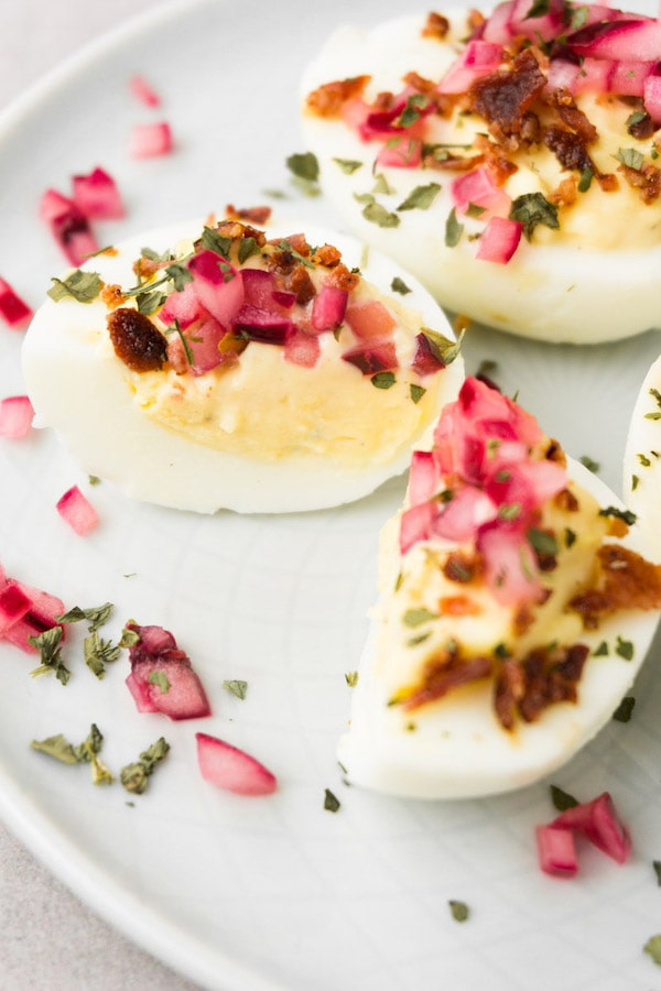 Cut in halve deviled egg topped with crispy bacon, pickled onions and herbs.