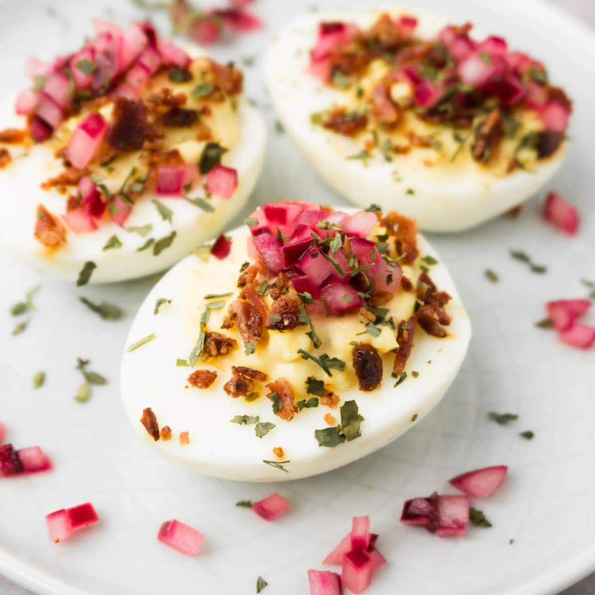 Close up shot of deviled eggs garnished with crispy bacon bits and pickled red onions.