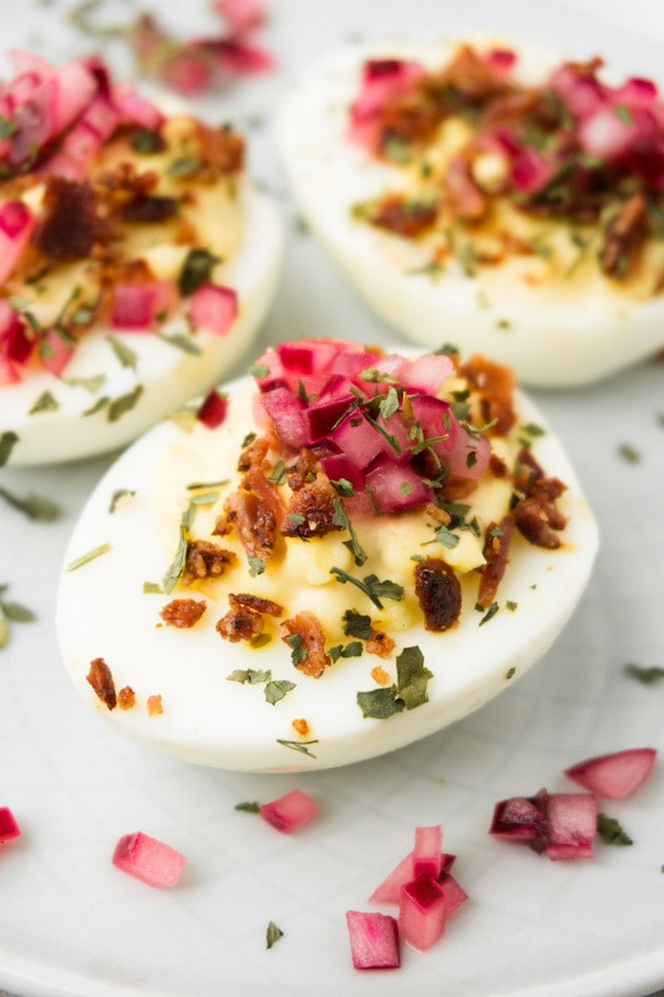 Close up shot of deviled eggs garnished with crispy bacon bits and pickled red onions served on a small round plate.