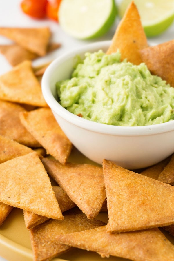 Plate full of tortilla chips with a small white bowl filled with guacamole in the centre.