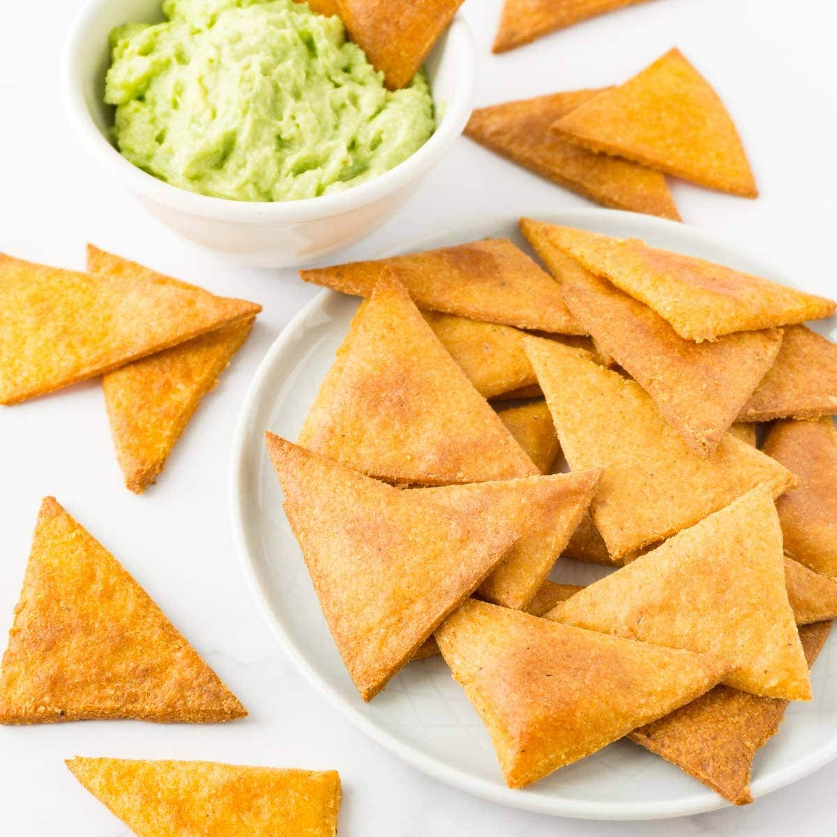 A small round plate with tortilla chips, more chips are lying around, bowl filled with guacamole on the background.