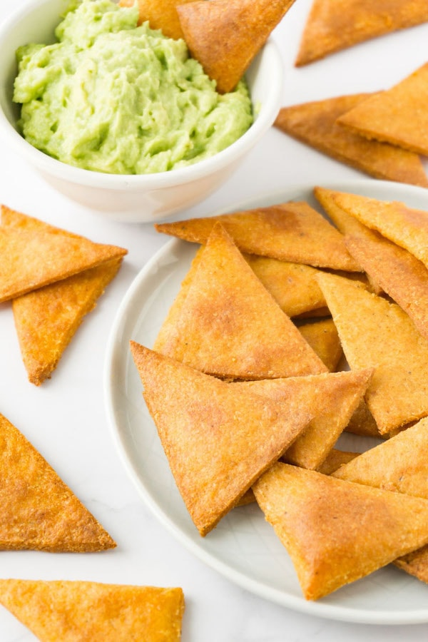 Tortilla chips on a small round plate, small bowl with guacamole on the background.