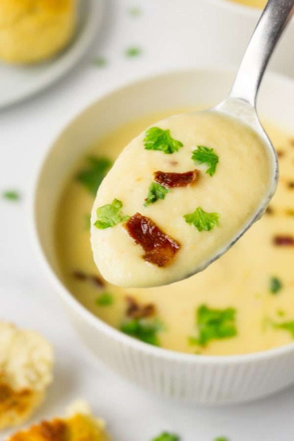 Spoon full of cauliflower soup with bacon bits and freshly-chopped parsley.