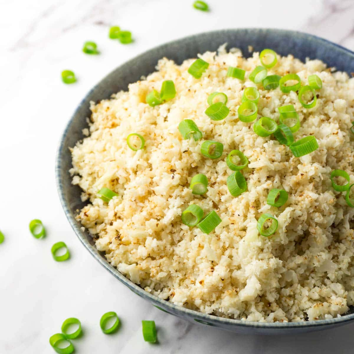 A close up shot of a large blue bowl filled with fluffy cauliflower rice garnished with freshly-chopped spring onions.