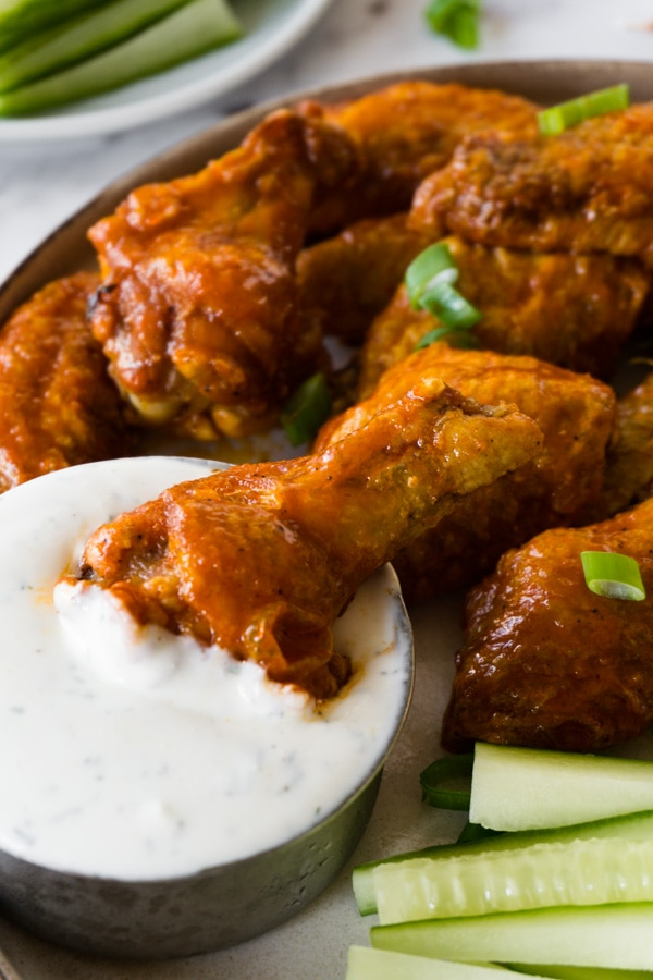 Buffalo wings on a plate with cucumber sticks and a small bowl filled with ranch dip, one drumettes is lying in the ranch dip bowl.