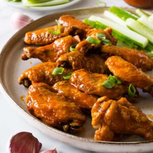 A large round plate with buffalo chicken wings garnished with chopped spring onions and cucumber sticks on the side.