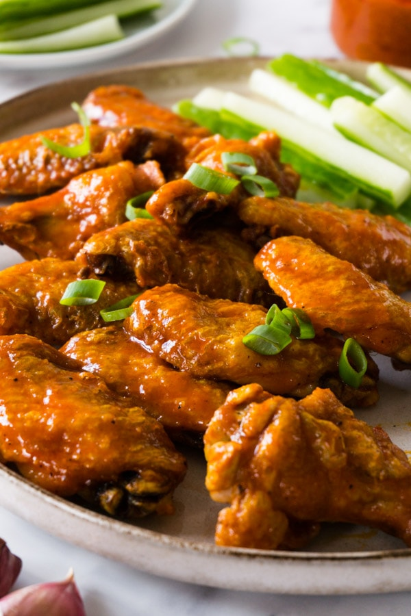 Chicken wings covered in buffalo sauce and garnished with freshly chopped spring onions on a plate with some cucumber stick on the side.