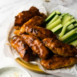 Buffalo chicken tenders on a plate lined with parchment paper, cucumber sticks on the back of the plate and ranch dip on the front.