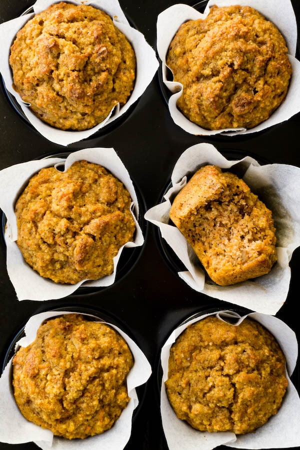 6 freshly baked carrot muffins in a muffin pan, one bite taken from one muffin.