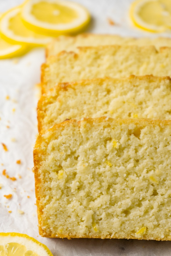 4 slices of lemon pound cake on a white parchment paper, fresh lemon slices and crumbs are lying around.