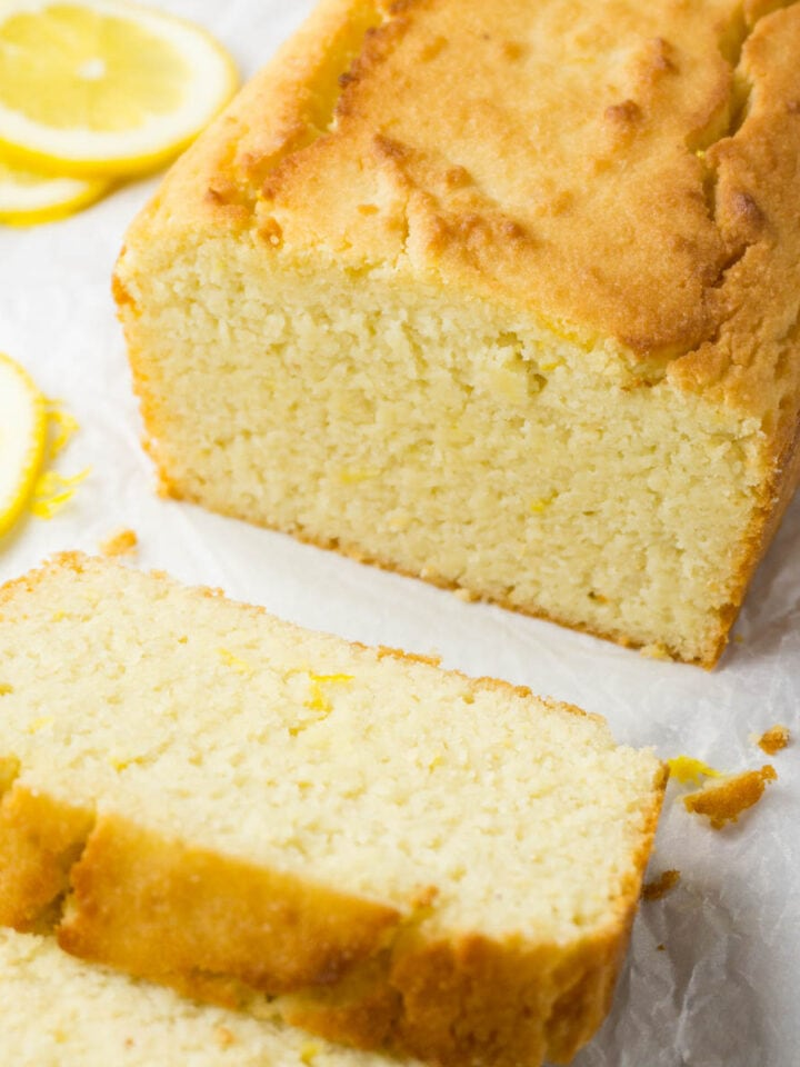 A close up shot of a lemon pound cake on a white parchment paper, several slices are lying in front.