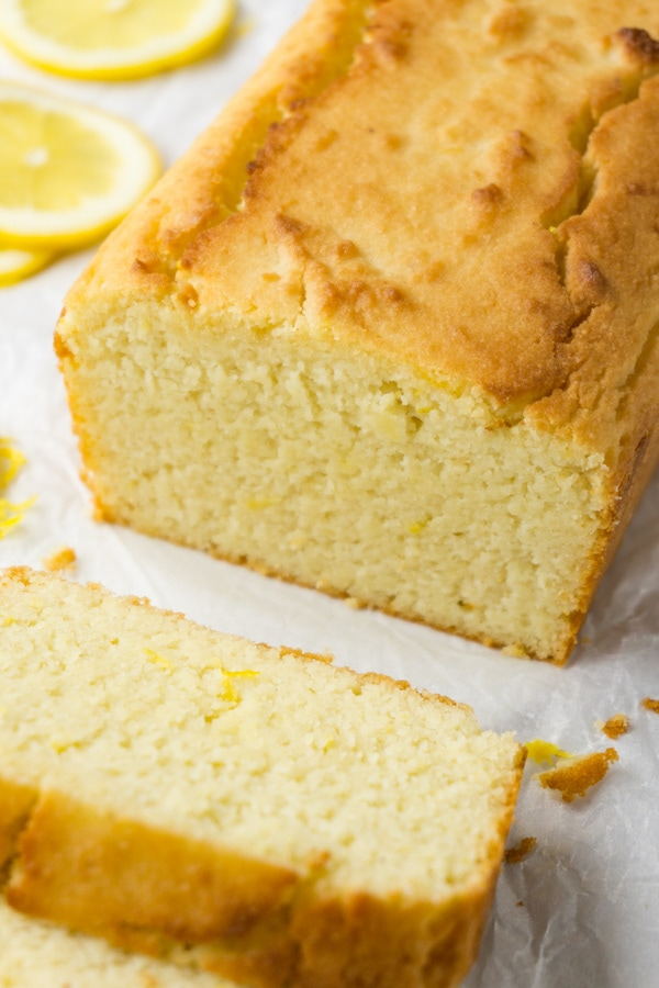 A partially sliced lemon pound cake on a white parchment paper, fresh lemon slices are on the background.