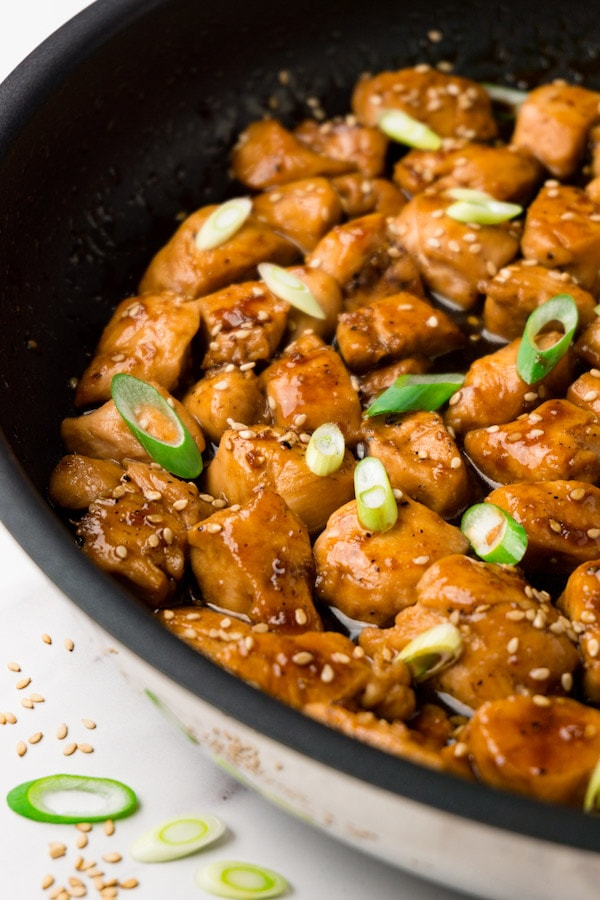 A large skillet with just made teriyaki chicken garnished with sesame seeds and chopped spring onions.