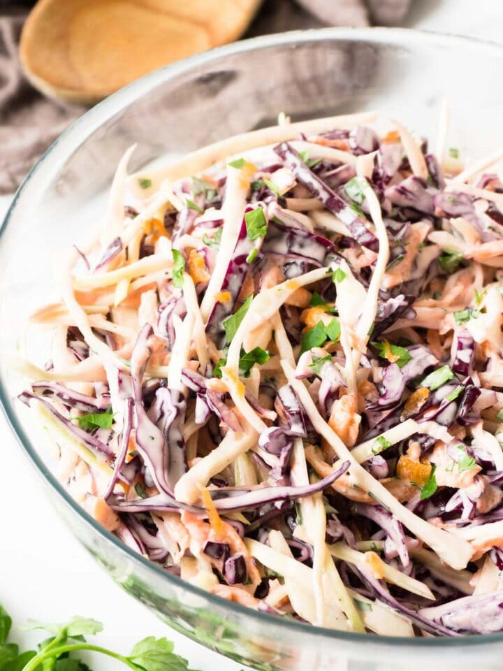 Close up shot of a glass bowl filled with cabbage coleslaw.