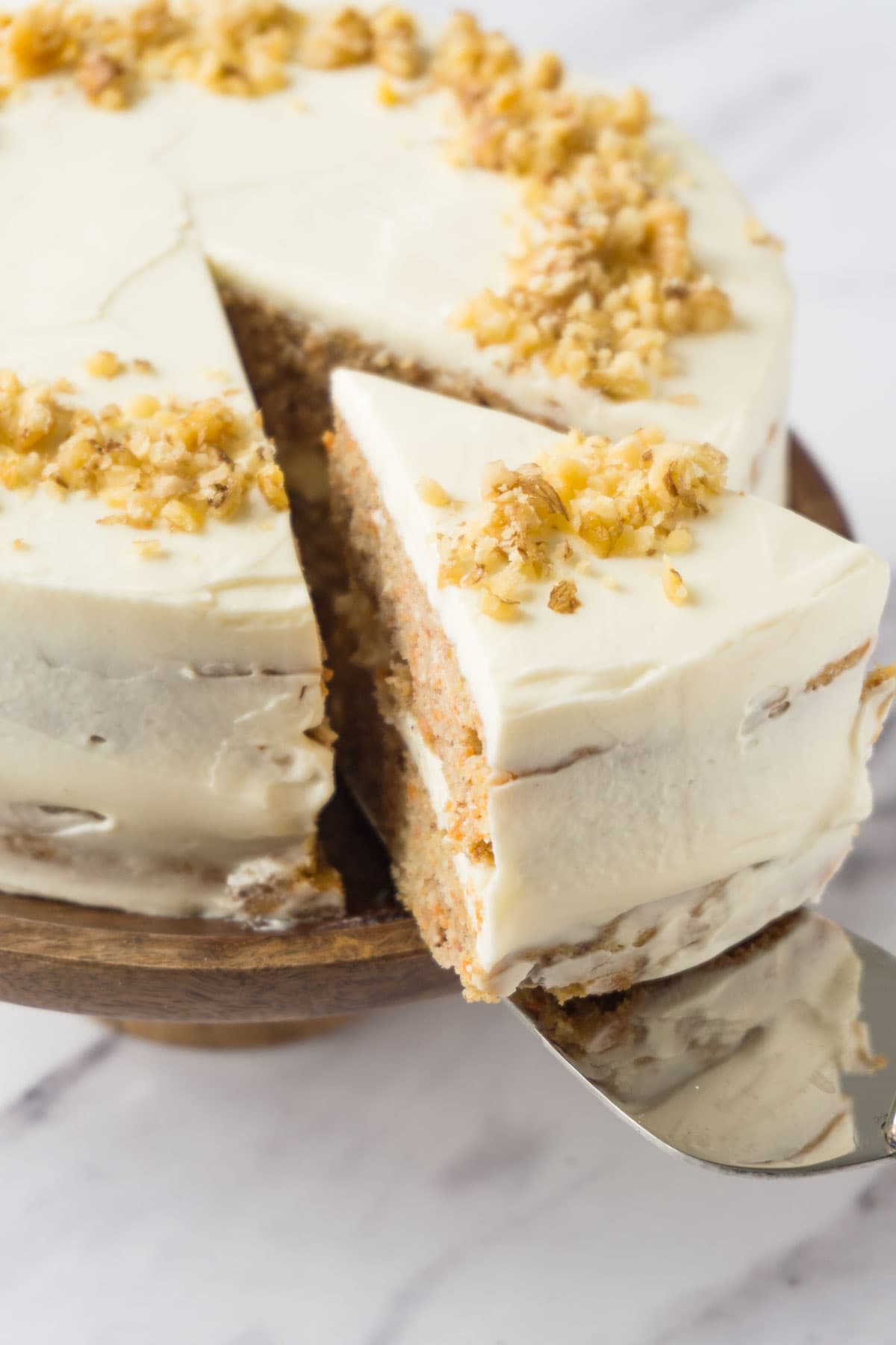 Taking a piece of carrot cake topped with crushed walnuts using a cake server.