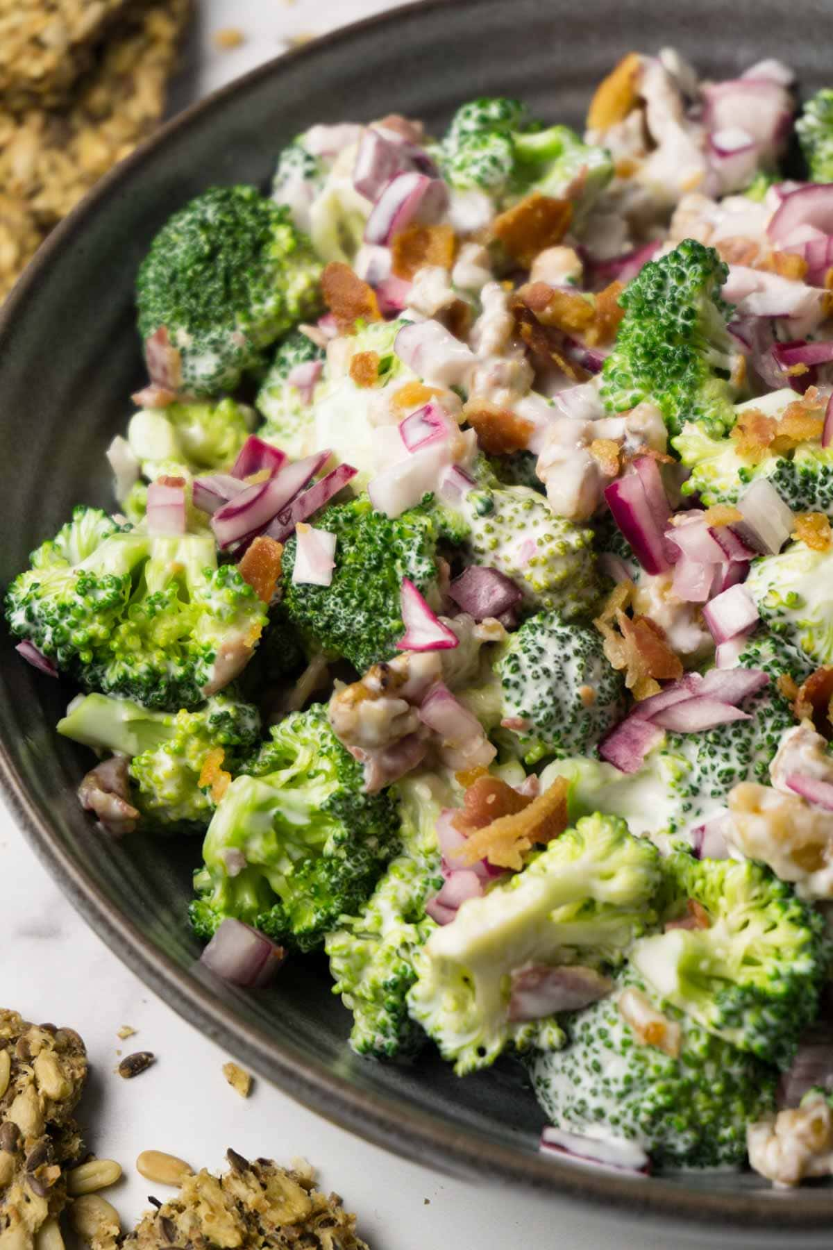 A dark round bowl filled with broccoli salad with bacon bits, red onions and walnuts with creamy dressing.