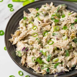 A grey round bowl filled with creamy chicken salad with celery and red onions, topped with chopped spring onions.