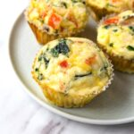 Freshly baked egg muffins on a small round plate.