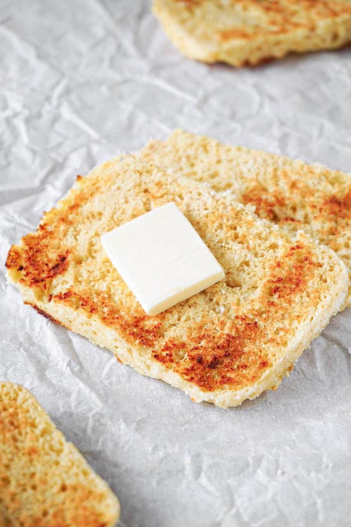 2 slices of microwave bread with some butter on top lying on a white parchment paper.
