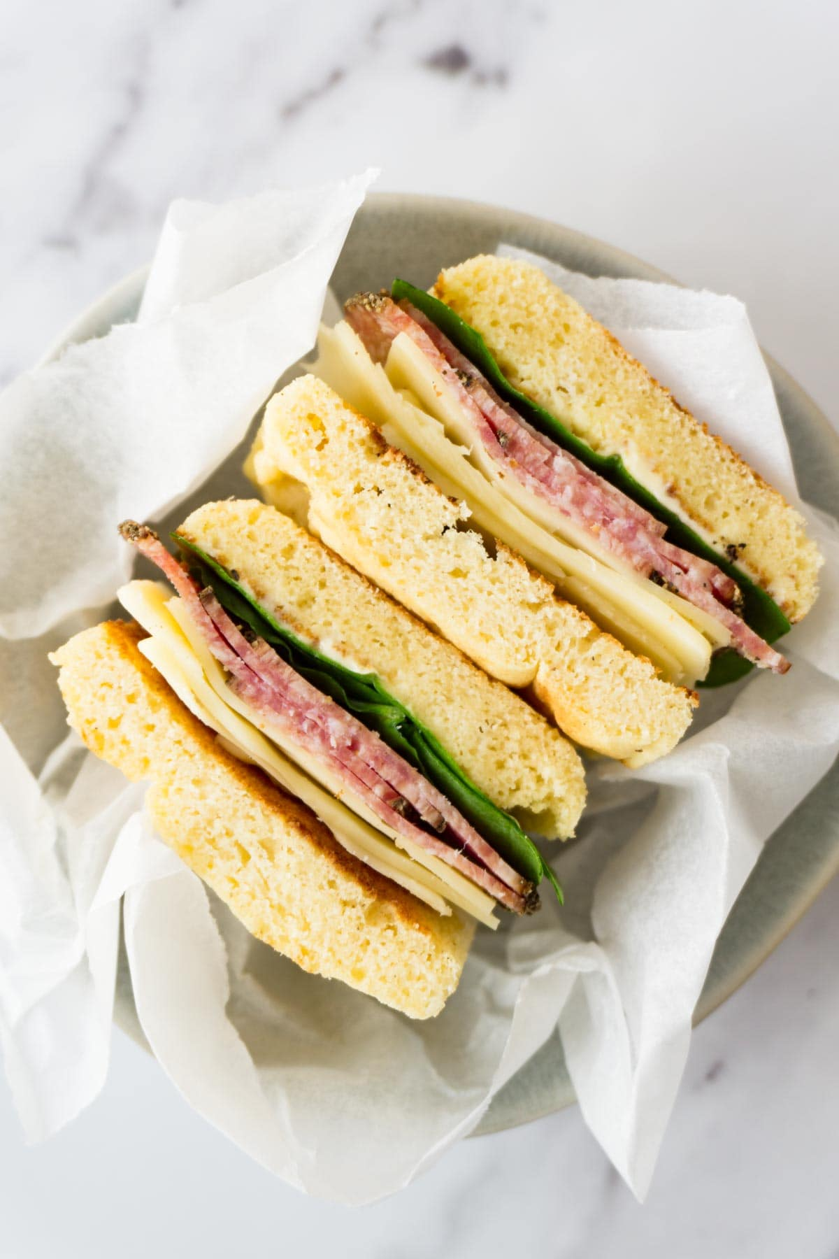 Two sandwiches with cheese, spinach, salami and keto bread in a small round bowl.
