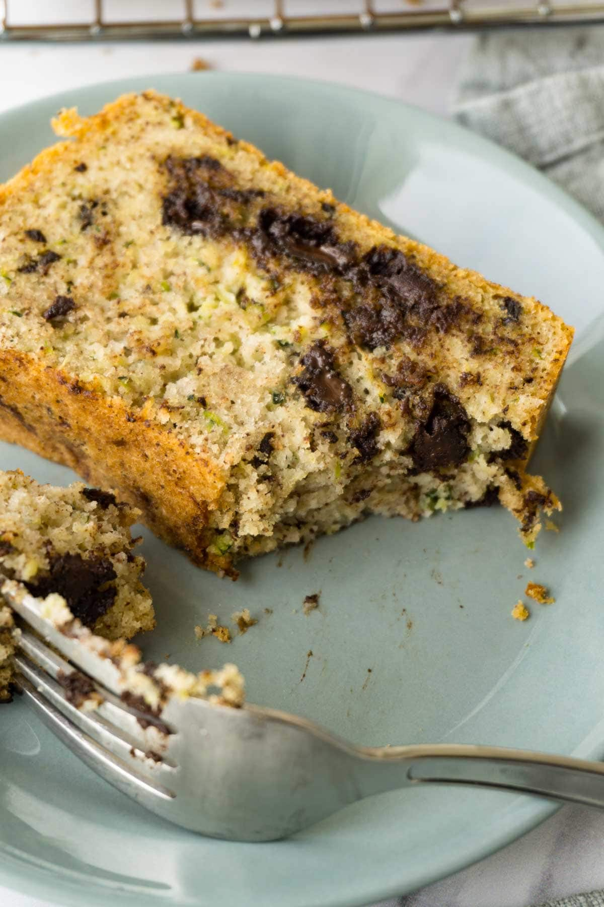 A slice of chocolate chip bread with zucchini on a small blue round plate, one piece taken with a silver fork.
