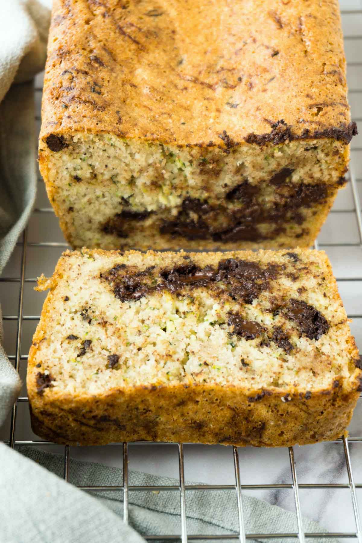 A partially sliced loaf bread with zucchini and chocolate chips on a cooling rack.