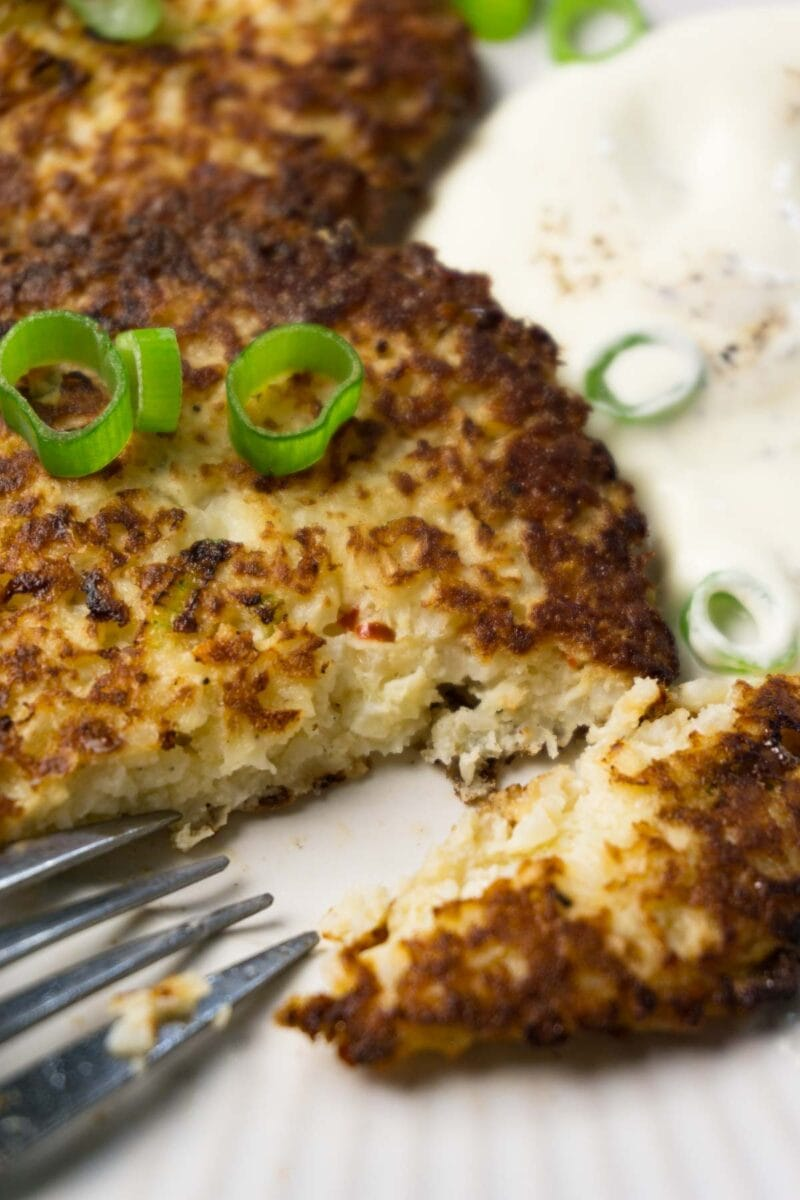 Close up shot of a cauliflower hash brown patty served on a plate with sour cream and fresh chopped green onions, one piece taken.