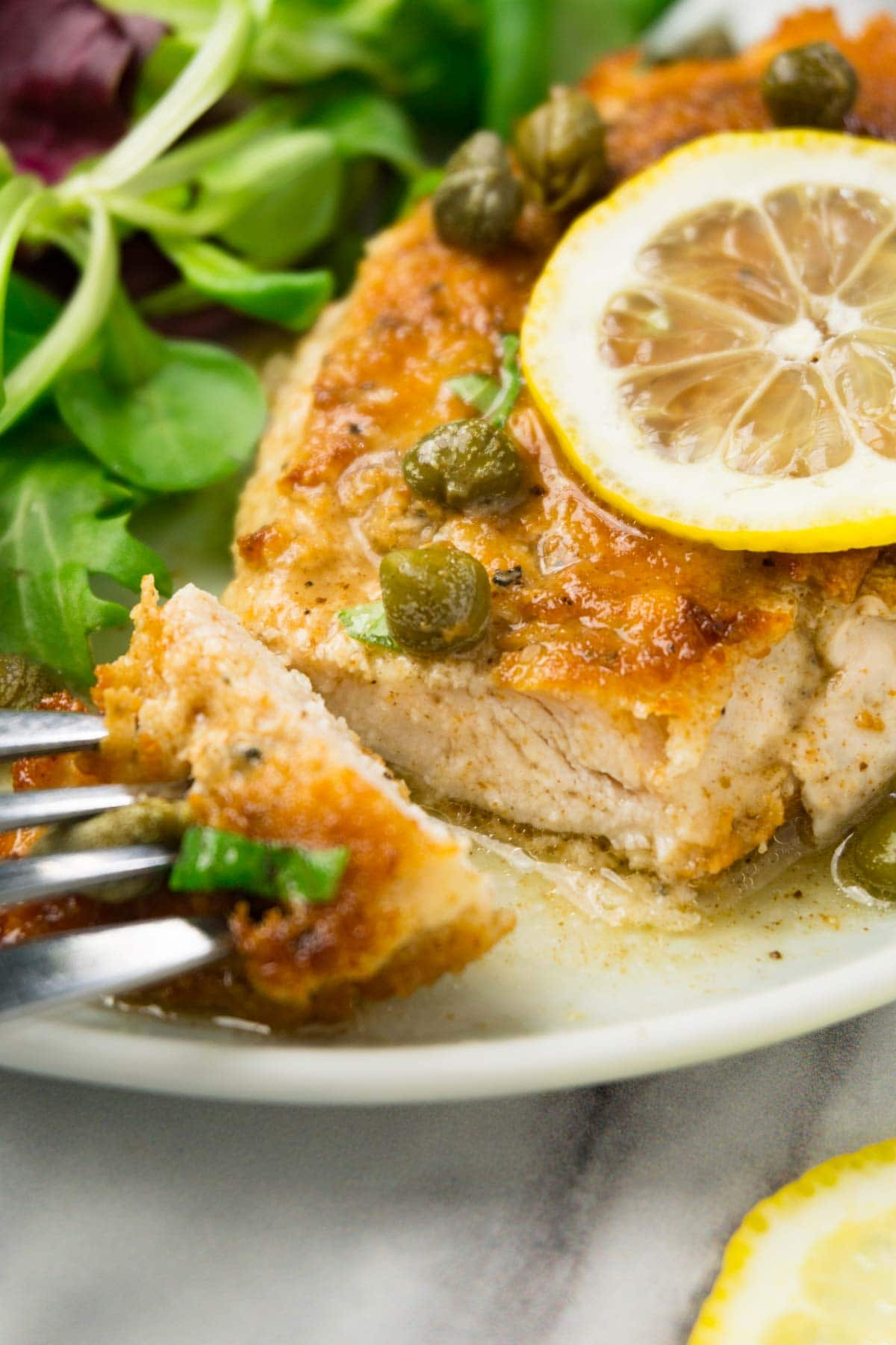 Chicken piccata on a plate garnished with fresh lemon slice and cappers, one piece is taken.
