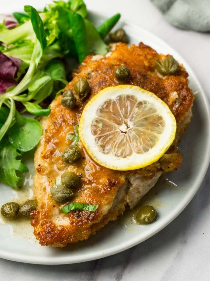Close up shot of a pice of chicken piccata with fresh salad on the side served on a small round plate.