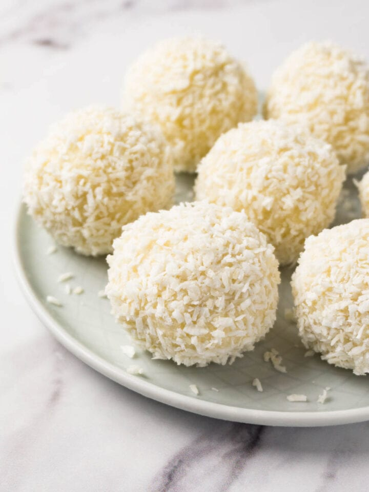 Cream cheese coconut balls covered in shredded coconut on a small round plate.