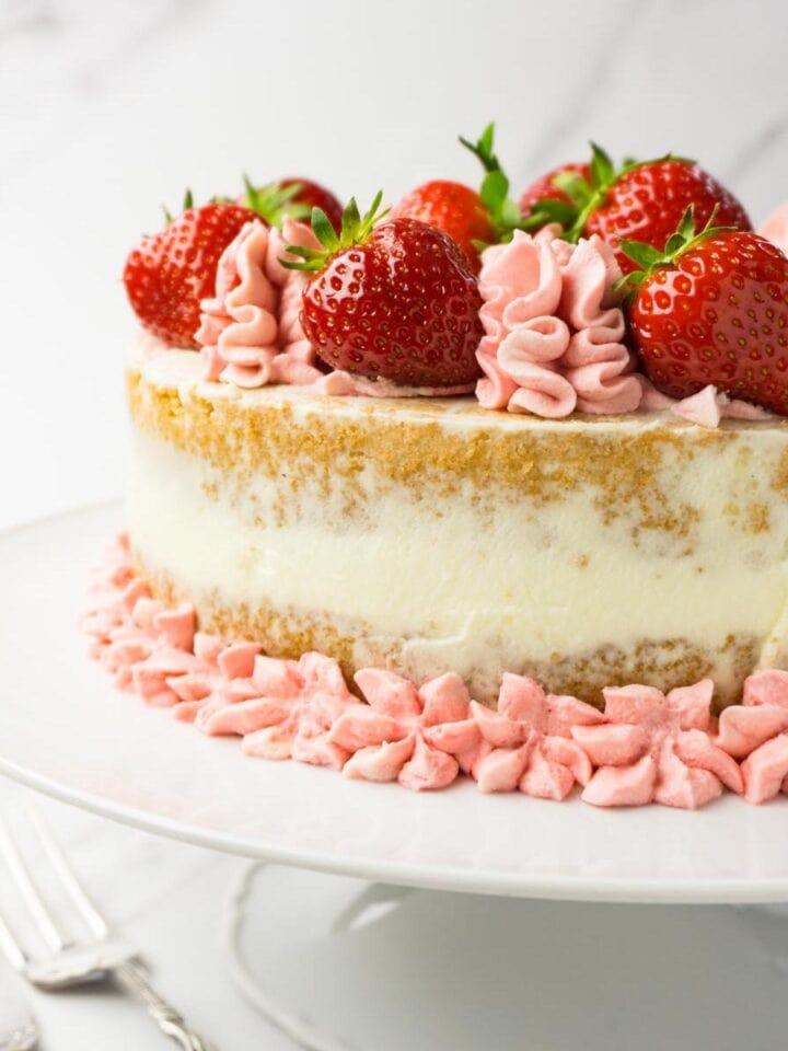 Close up shot of a strawberry cake decorated with pink frosting and fresh strawberries on a white cake stand.