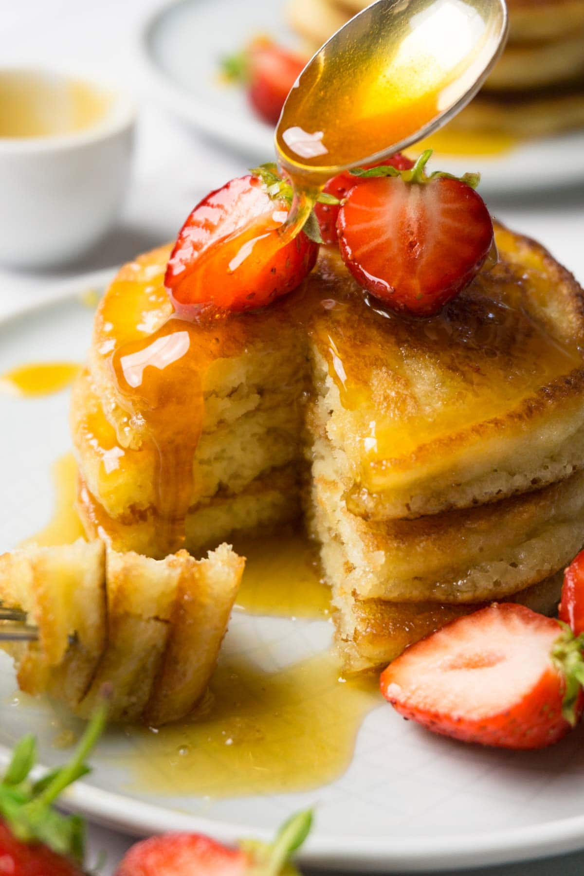 Pancake tower on a plate topped with fresh strawberries, a spoon drizzling syrup on top.