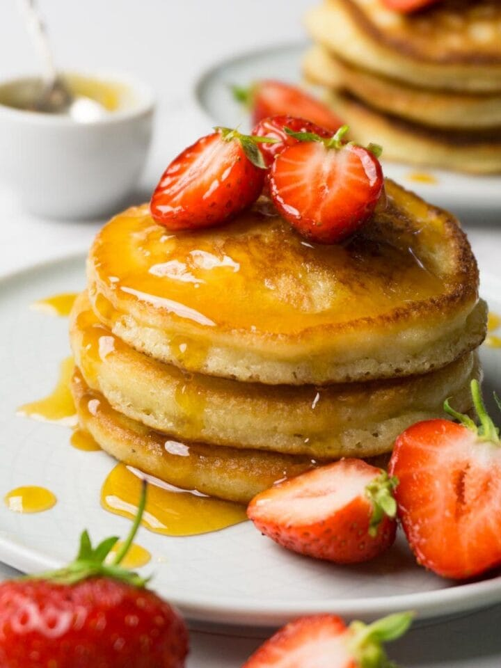 Three pancakes stacked one on top of each other, topped with fresh strawberries and sugar-free syrup.