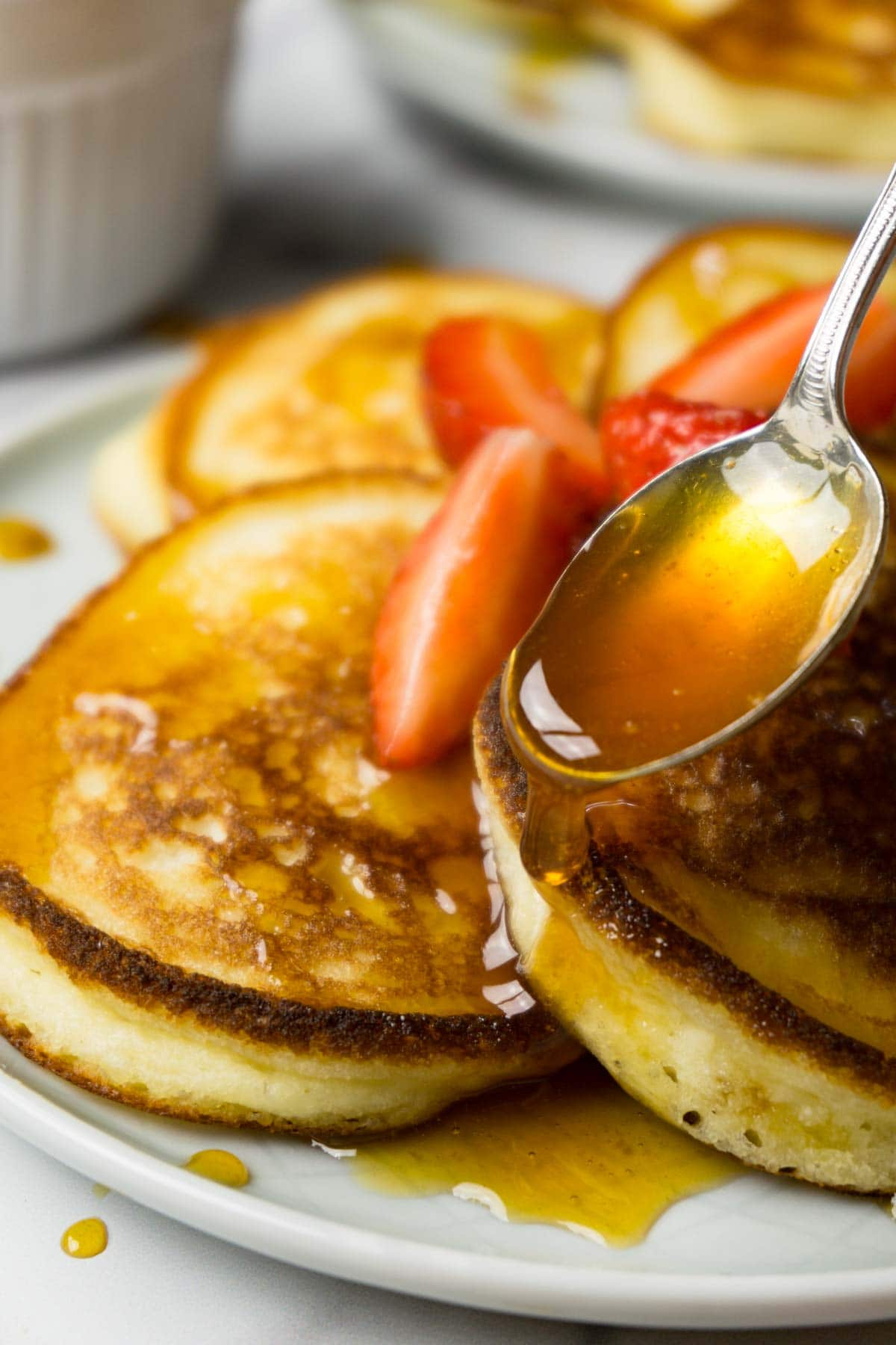A silver spoon is pouring sweet syrup on the pancakes garnished with fresh strawberries.