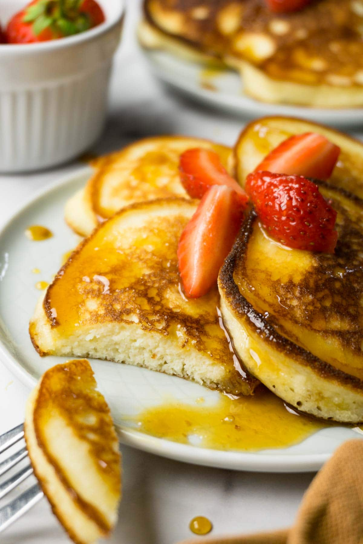 Pancakes on round plate with strawberries and sugar-free syrup, one piece is missing from one pancake.