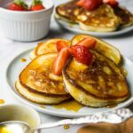 A small round plate with 4 pancakes topped with fresh strawberries and syrup, one more plate with pancakes on the background.