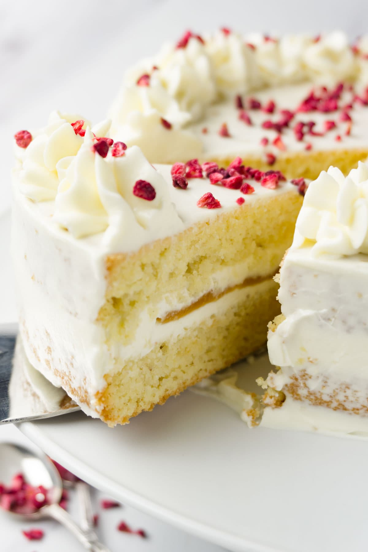 An assembled vanilla cake with caramel filling and cream cheese frosting topped with freeze-dried raspberries, one piece cut and coming out.