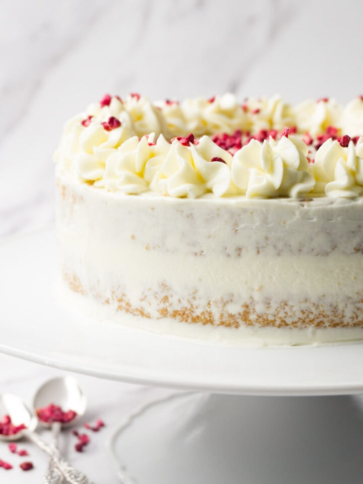 Vanilla caramel cake frosted with cream cheese frosting and decorated with freeze-dried raspberries on a white cake platter.