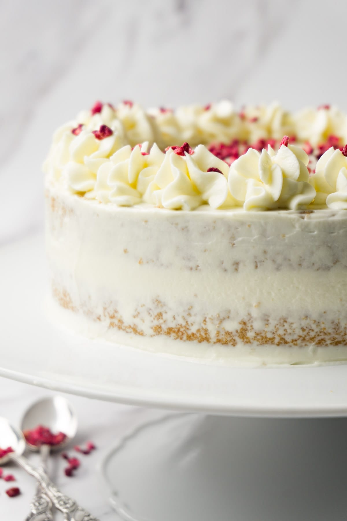 Halve naked low carb vanilla caramel cake with cream cheese frosting and decorated with freeze-dried raspberries on a white cake platter.