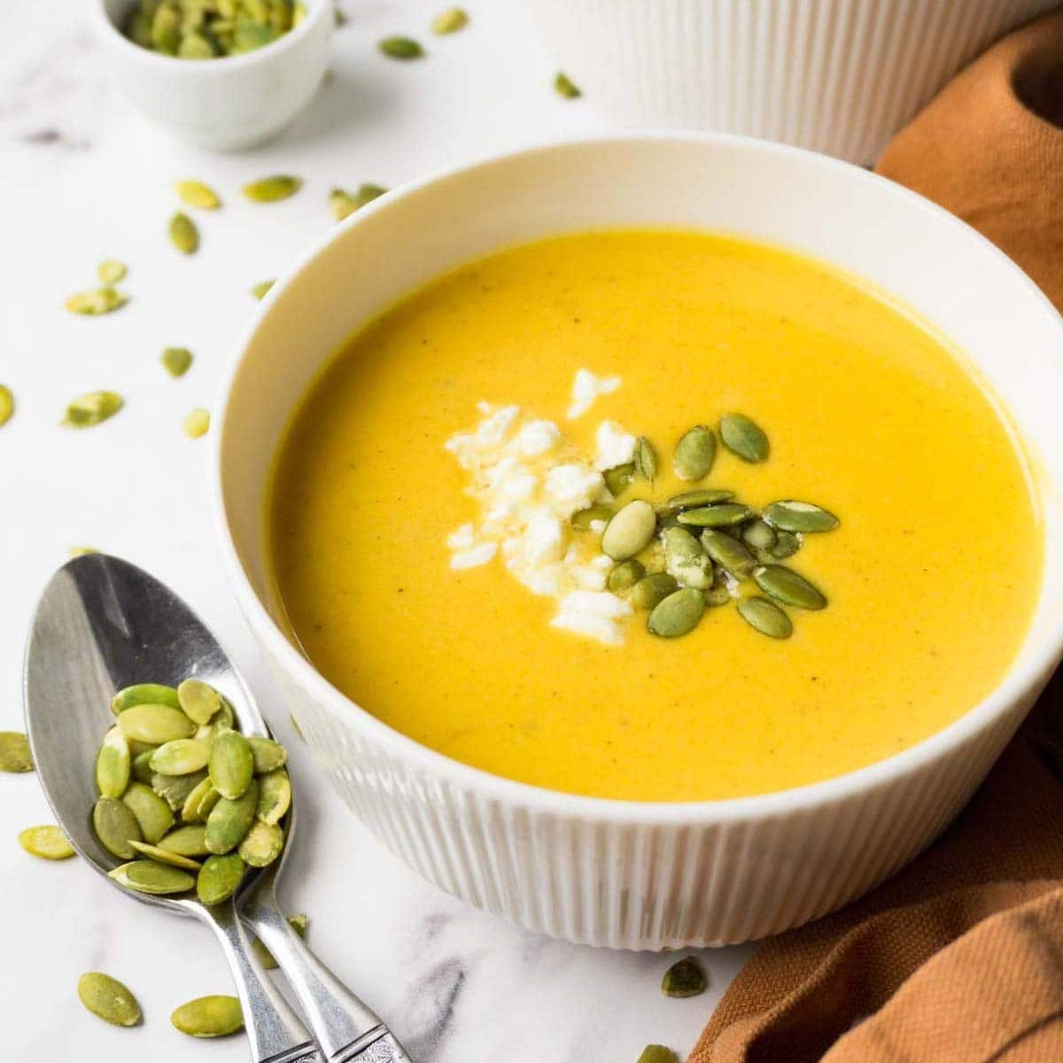 A white bowl filled with butternut squash soup garnished with pepitas and crumbled feta cheese.