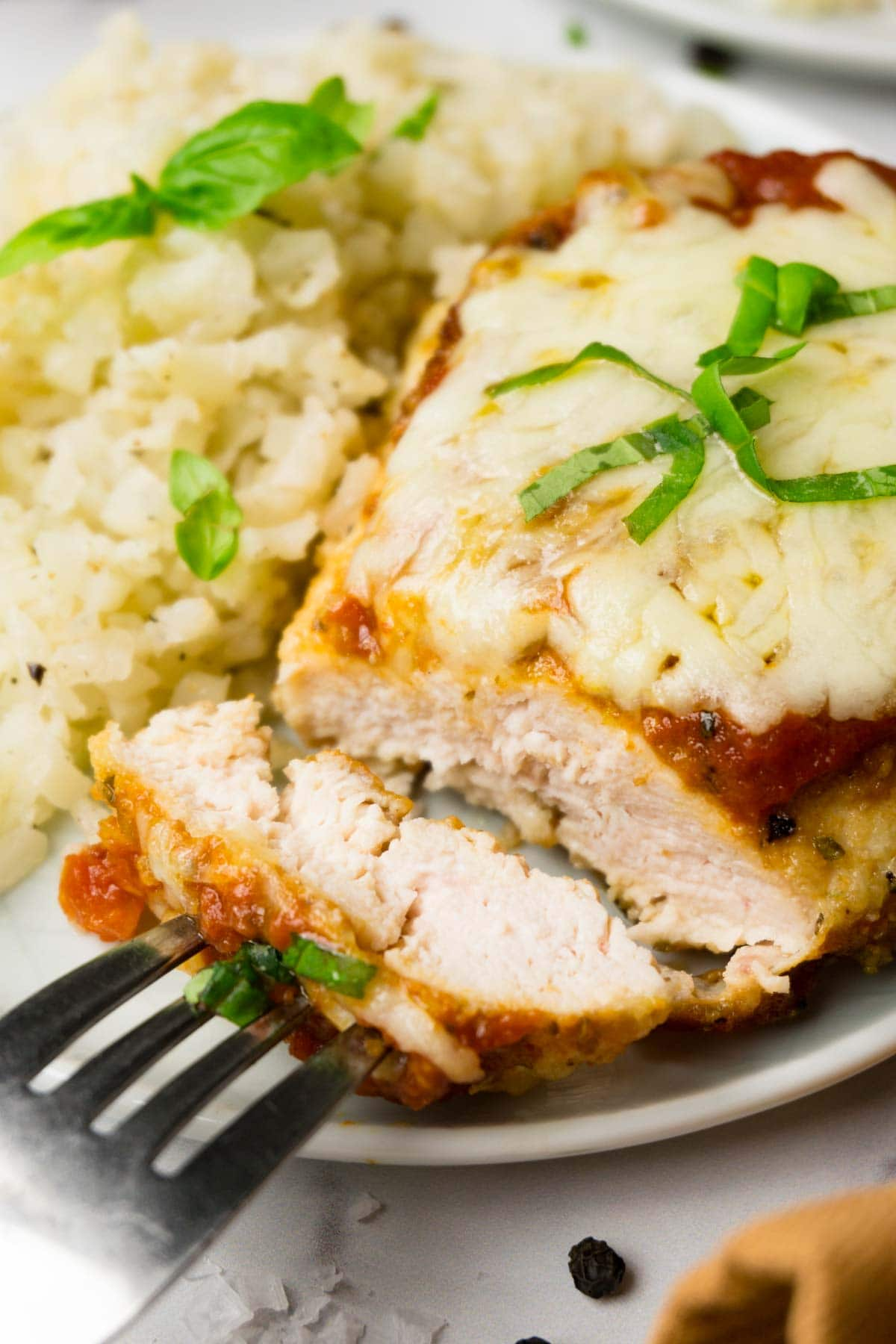 Chicken parmesan on a small round plate with cauliflower rive on the side, one piece of the chicken taken.