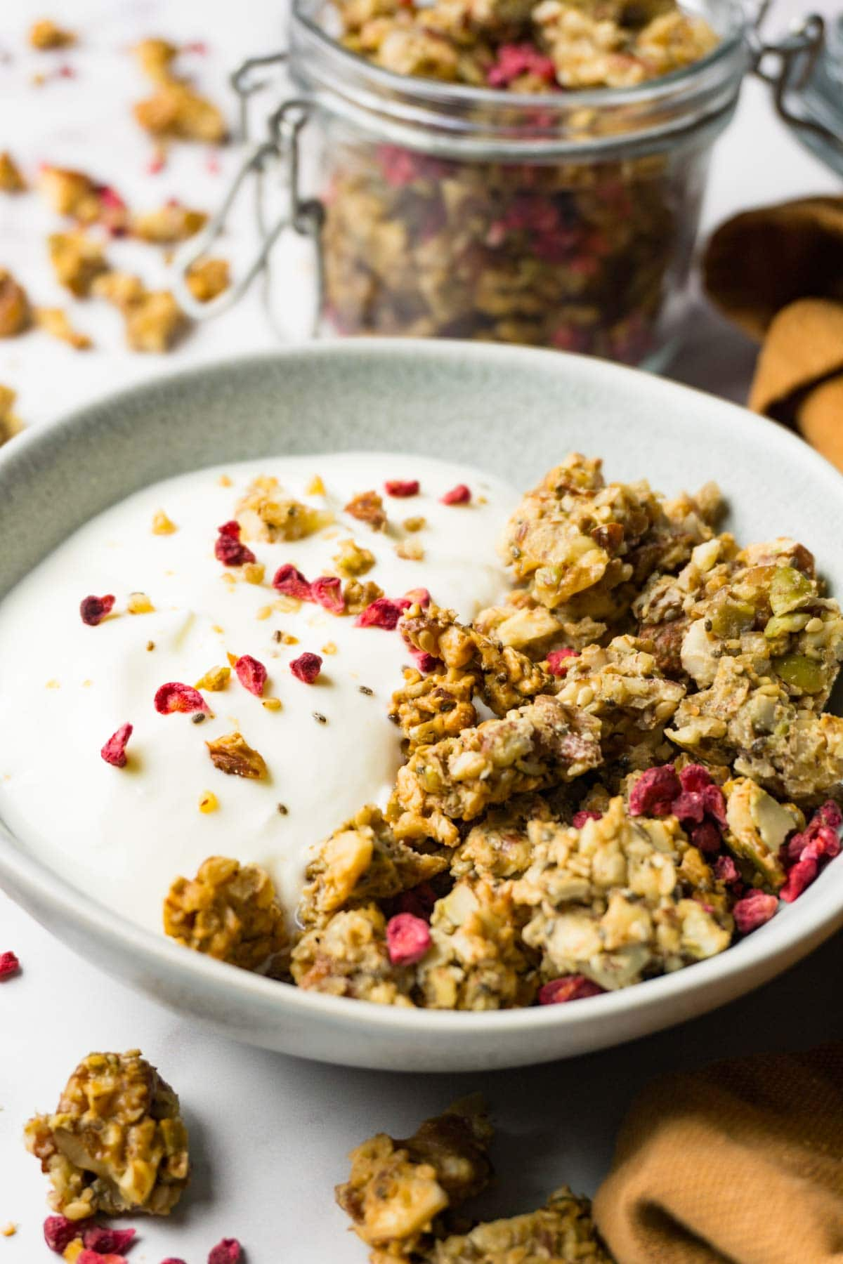 A small round bowl with yoghurt and nuts and seeds granola topped with freeze-dried raspberries, a glass jar with granola on the background.